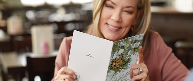 A woman is smiling as she reads a holiday-themed greeting card.