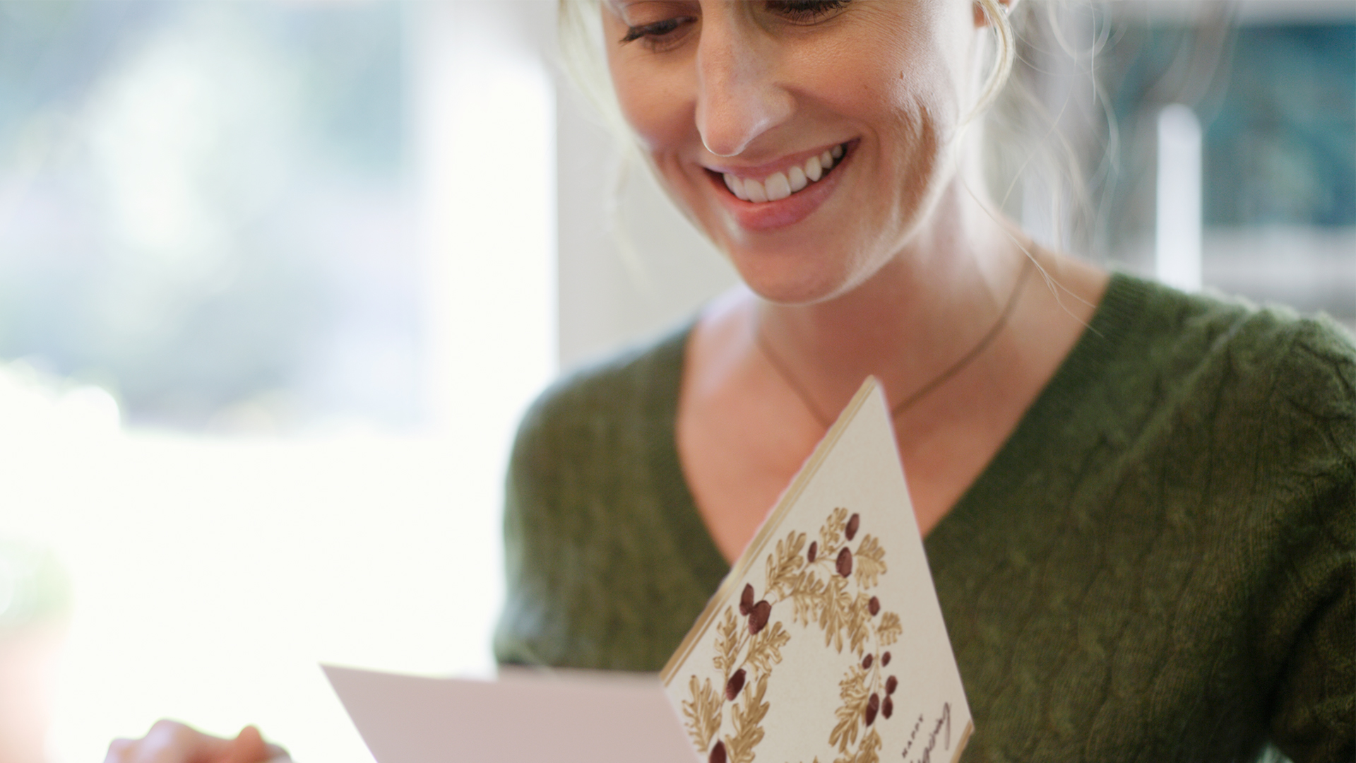 A woman, smiling, looks at an open Thanksgiving card, taking in the personal message.  a card would be an unexpected and meaningful moment.