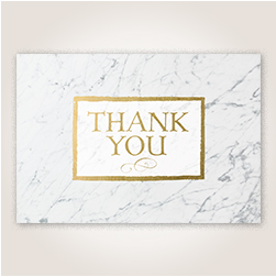 A simple Thank You artisanally embellished with gold foil sits on top a sophisticated white and gray marble background.